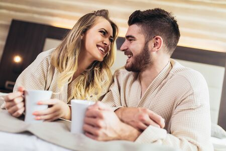 Young happy couple drink coffee in luxury hotel room.
