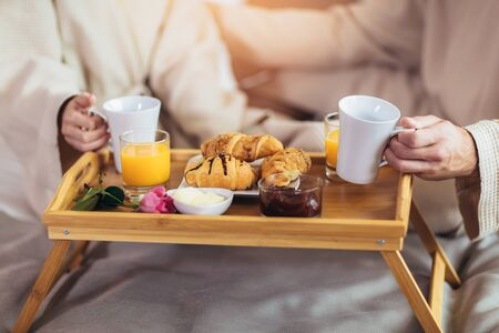 Couple having breakfast in luxury hotel room, close up. Stock Photo