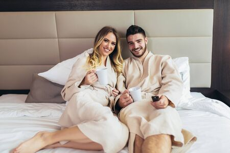 Young happy couple having breakfast in luxury hotel room, watching TV. Stock Photo