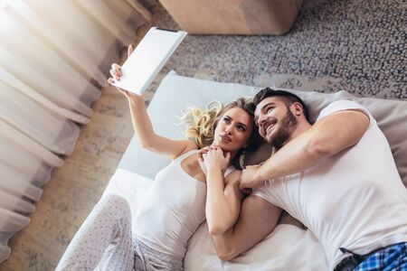 Happy young couple lying on the bed in a bedroom and using digital tablet.