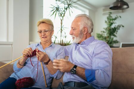 Senior woman teaching her husband the art of knitting woollen clothes. Stockfoto - 127036791