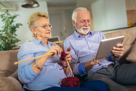 Senior woman knitting woollen clothes and her husband is using digital tablet.