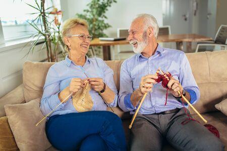 Senior woman teaching her husband the art of knitting woollen clothes. Stockfoto - 127036797