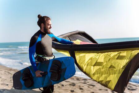 Bel homme de race blanche surfeur professionnel debout sur la plage de sable avec son cerf-volant