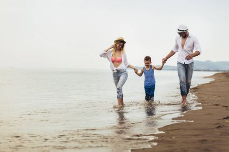 Mother and father with their son walking together on a quiet beach.
