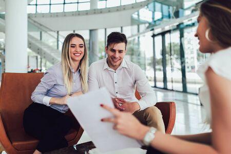 Doradca finansowy pokazujący młodej parze raport dotyczący ich inwestycji. Sprzedawca i pozytywna para rozmawiają o zakupie. Szczęśliwa para konsultacji agenta finansowego o pożyczkę.