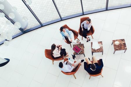 Group of young business professionals sitting together and having casual discussing in office hallway achieving goals. Top view.