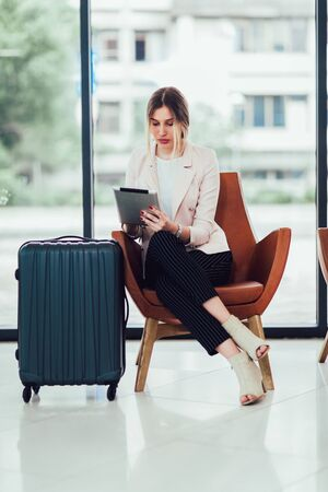 Business woman sitting in airport and waiting for her flight