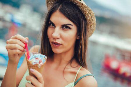 Frau isst draußen Eis im Sommerurlaub im Urlaubsort. - Standard-Bild