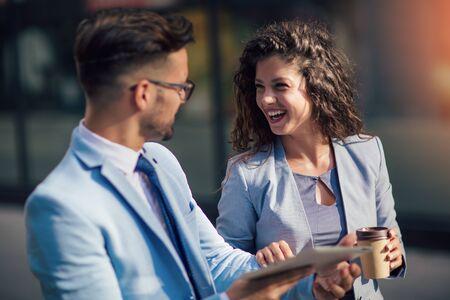 Hombre guapo y mujer hermosa como socios comerciales con tableta digital al aire libre Foto de archivo