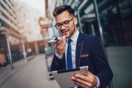 Young business man using voice command recorder on smartphone. Banque d'images