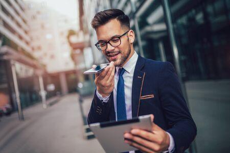 Junger Geschäftsmann mit Sprachbefehl-Recorder auf dem Smartphone.