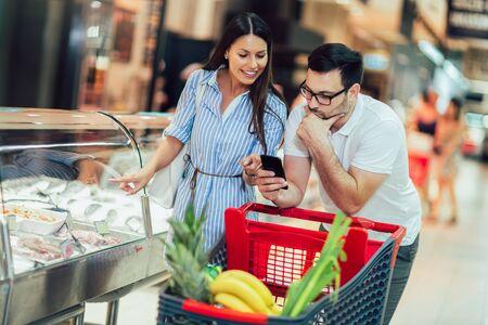 Glückliches junges Paar, das sich miteinander verbindet und beim Gehen im Lebensmittelladen mit Einkaufswagen lächelt?