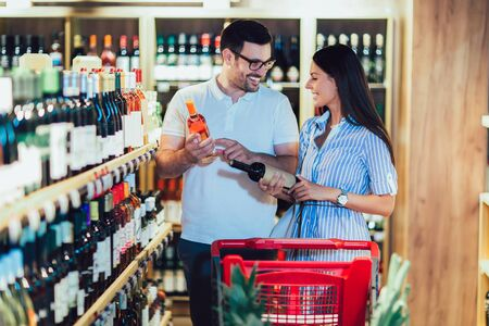 Happy couple shopping in supermarket buying wines Stockfoto