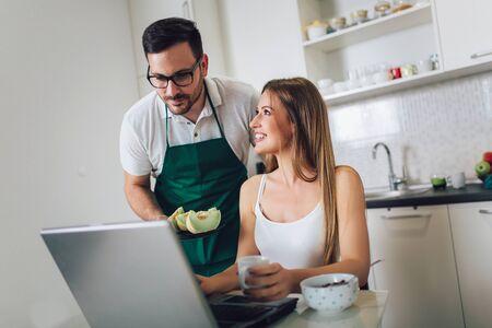 Woman working on laptop in kitchen as boyfriend prepares meal. Standard-Bild