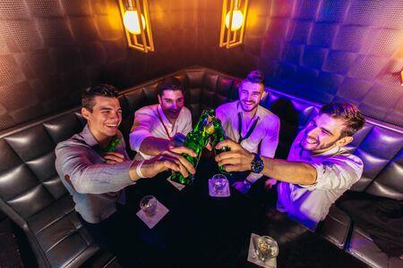 Gruppe junger Männer, die in einem Nachtclub anstoßen Standard-Bild