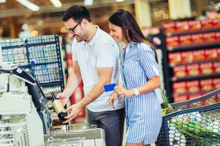 Paar mit Bankkarte beim Kauf von Lebensmitteln im Supermarkt oder an der Selbstkasse im Supermarkt