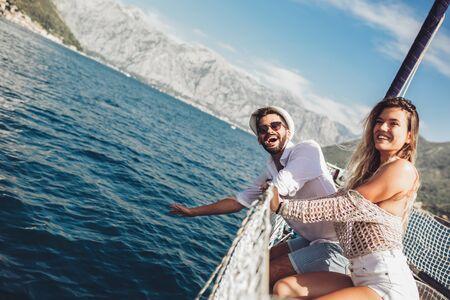 Liebespaar, das glückliche Zeit auf einer Yacht auf See verbringt. Luxusurlaub auf einem Seeboot. Standard-Bild