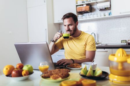 Busy man working at home, using laptop while having breakfast.