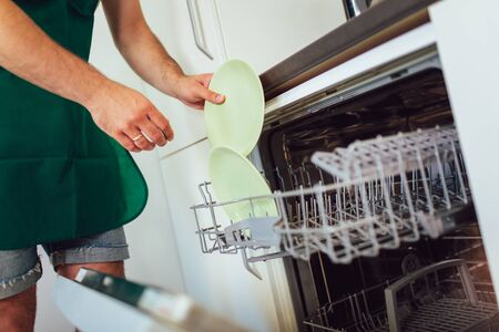 close-up of male hands loading dirty dishes to the dish washing machine
