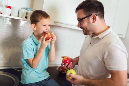 Happy father and kid standing in kitchen in embrace. They holding fruit in hands