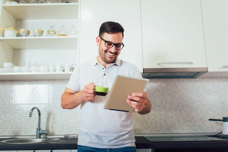Happy man using digital tablet in kitchen at home