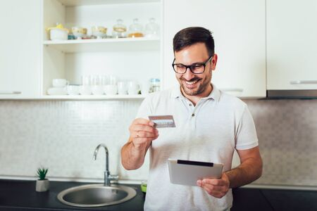 Happy man using digital tablet and credit card in kitchen at home 版權商用圖片