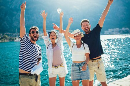 Happy group of tourists traveling and sightseeing together near the sea