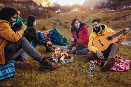 Group of smiling friends sitting around bonfire in camping