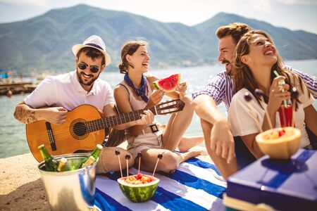 Young people having fun on summer vacation.Happy friends drinking tropical cocktails on the beach. Banque d'images