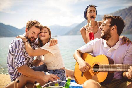 Junge Leute, die Spaß im Sommerurlaub haben. Glückliche Freunde, die tropische Cocktails am Strand trinken. Standard-Bild