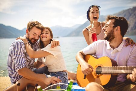 Young people having fun on summer vacation.Happy friends drinking tropical cocktails on the beach. Stock Photo