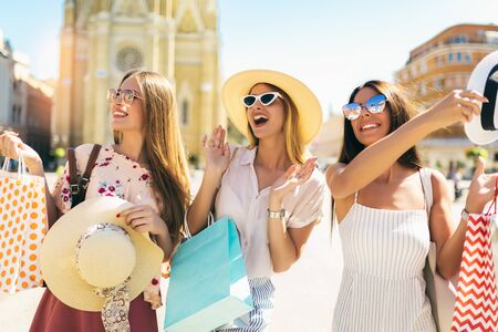Three beautiful girls in sunglasses with shopping bags in city. Stock Photo