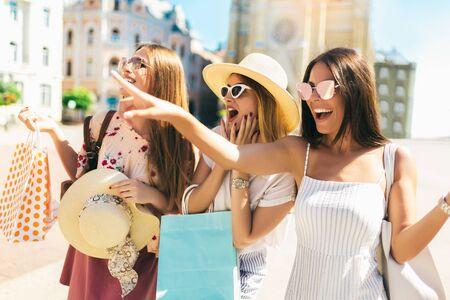 Tre belle ragazze in occhiali da sole con borse della spesa in città.