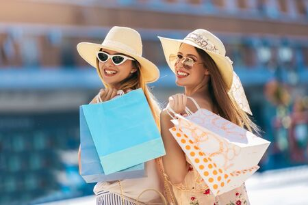 Two beautiful girls in sunglasses with shopping bags in city.