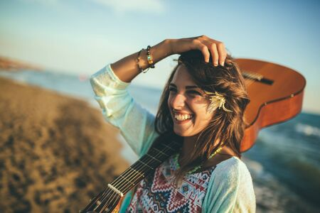 Cute girl walking on the beach holding a guitar in her hands.