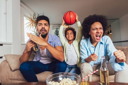 Happy African American family of three watching tv and cheering sport games on sofa at home Stockfoto - 128615462