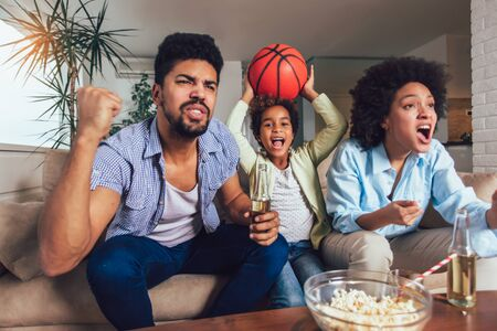 Happy African American family of three watching tv and cheering sport games on sofa at home Stockfoto - 128615463