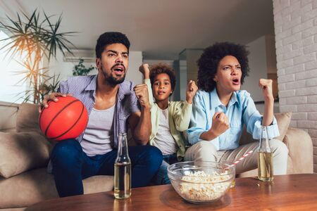 Happy African American family of three watching tv and cheering sport games on sofa at home Stockfoto - 128615464
