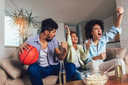 Happy African American family of three watching tv and cheering sport games on sofa at home Stockfoto - 128615466