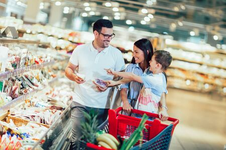 Happy family with child and shopping cart buying food at grocery store or supermarket Banque d'images