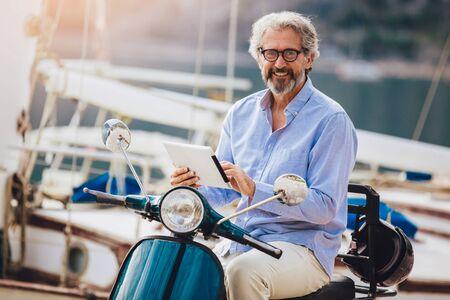 Mature man on motor scooter holding digital tablet in marina.