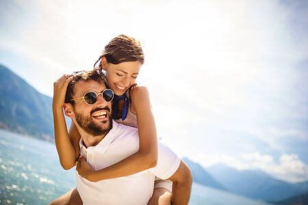 Handsome young man giving piggyback ride to girlfriend on beach. Romantic young couple enjoying summer holidays. Stok Fotoğraf