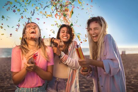 Happy young people having fun at beach party, celebrating with confetti. Banco de Imagens