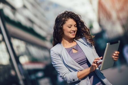 Young business woman using digital tablet outdoor