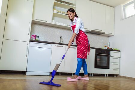 Young woman washing floor on the kitchen Banque d'images - 129738838