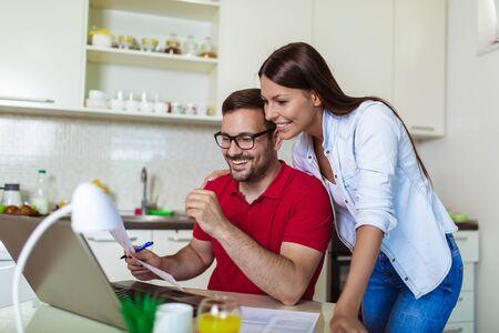 Pareja joven administrando las finanzas, revisando sus cuentas bancarias usando una computadora portátil en la cocina moderna.