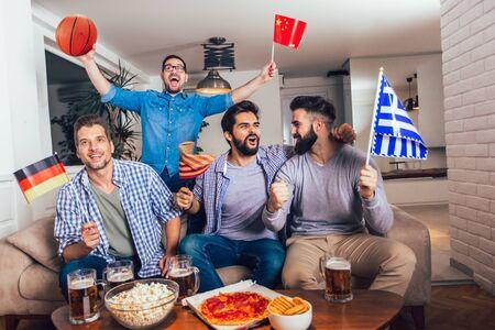 Amigos felices o fanáticos del baloncesto viendo el partido de baloncesto en la televisión y celebrando la victoria en casa. Concepto de amistad, deportes y entretenimiento. Foto de archivo
