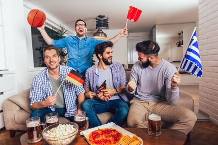 Happy friends or basketball fans watching basketball game on tv and celebrating victory at home.Friendship, sports and entertainment concept. 版權商用圖片 - 129739019