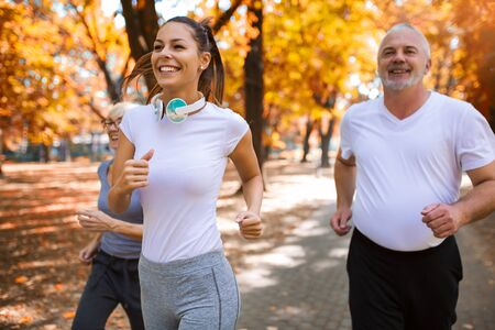 Senior man and woman and young female instructor workout on fresh air. Outdoor activities, healthy lifestyle, strong bodies, fit figures. Stylish, modern sportswear. Stock Photo